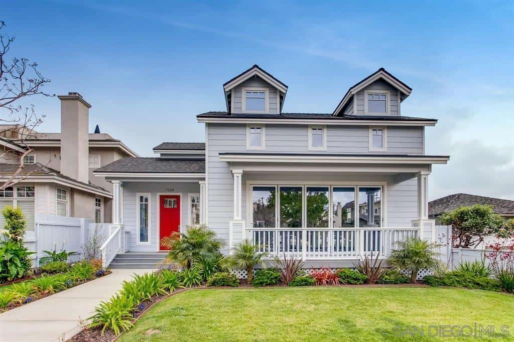 This is a Craftsman-Style wooden house that has two dormer windows and a row of glass doors leading to a porch that looks over the front lawn. The light hues of the walls and windows are contrasted by a bright red wooden main door to give it a charismatic personality.