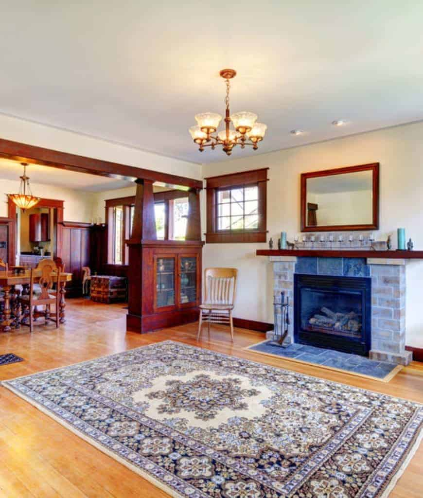 Spacious living room with a stone brick fireplace and a classy floral rug lighted by a warm chandelier.