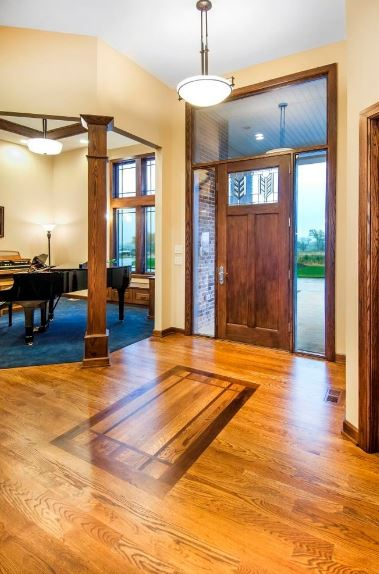 The dome-shaped pendant lighting of this foyer shines a warm yellow light on the wooden tones of the floor and a wooden main door that is fitted with a pair of glass side lighting. The hardwood floor has a patterned design burnt into its wood that mirrors the door.