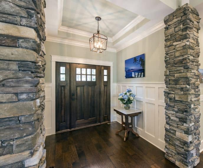 This Craftsman-Style foyer has a dark wooden main door that has matching side lighting that are illuminated by the pendant light hanging in the middle of the tray ceiling. This foyer is bordered with a pair of stone pillars that stand out against the white wooden finish of the walls.