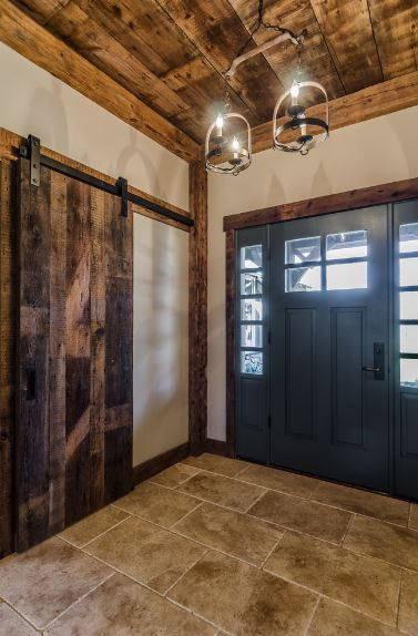 The burnt wood details of this Craftsman-Style foyer give it a farmhouse greeting that is enhanced by the wooden sliding door and dark iron lighting hanging from the ceiling. This is counterbalanced by the smooth traditional green main door paired with white walls.