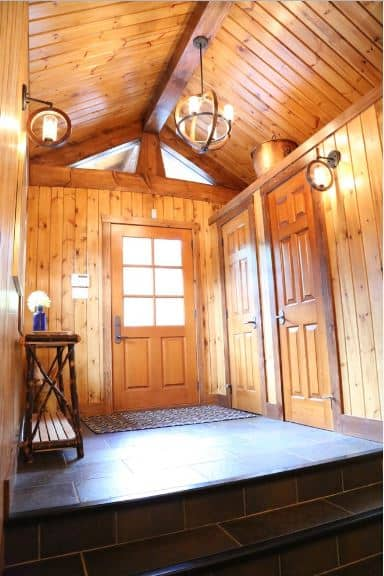 The ceiling of this Craftsman-Style foyer is reminiscent of a cottage with its wooden cathedral finish that has a single exposed beam that supports a spherical pendant light. This pendant light matches well with the wall-mounted lamps that illuminate the dark tiles of the floor.