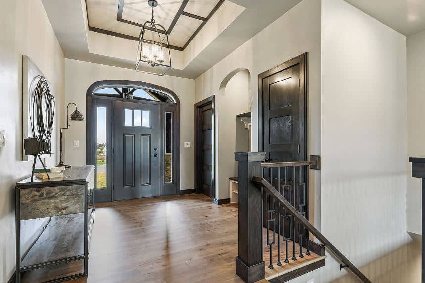 This Craftsman-Style foyer has an elegant tray ceiling that has a brilliant chandelier hanging in the middle. This chandelier has a dark iron fitting that mirrors the dark hue of the doors, staircase railing, and the console table topped with a wall-mounted artwork.