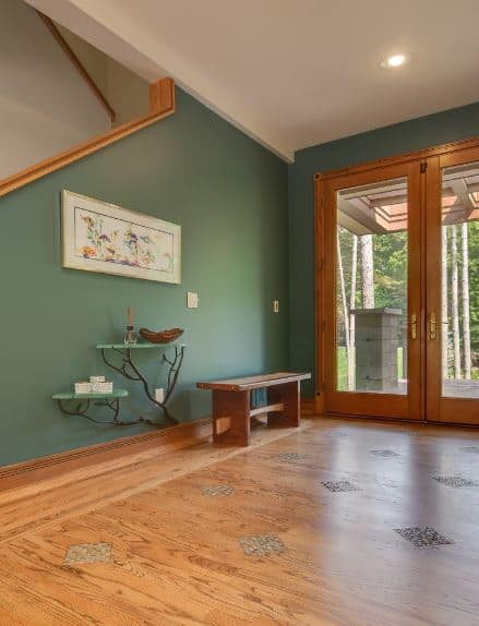 This Craftsman-Style foyer has a greeting that mirrors the nature outside the house. It has glass double doors that are framed with the same wooden palette as the hardwood flooring. A lovely wooden bench stands on the side that is paired with quaint wall-mounted tables adorned with branches that sprout from the green wall.