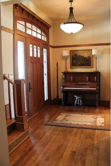 This Craftsman-Style foyer welcomes the guests with an elegant wooden piano that is adorned with table lamps flanking a wall-mounted painting. The hardwood flooring matches well with the wooden door and its side lights and transom window.