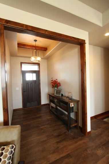 The tray ceiling of this Craftsman-Style foyer has wooden exposed beams that pairs with the finish of the entryway. This stands out against the white walls and a white ceiling that are illuminated by a modern pendant lighting. The dark wooden door is paired with a transom window that brings in natural light.