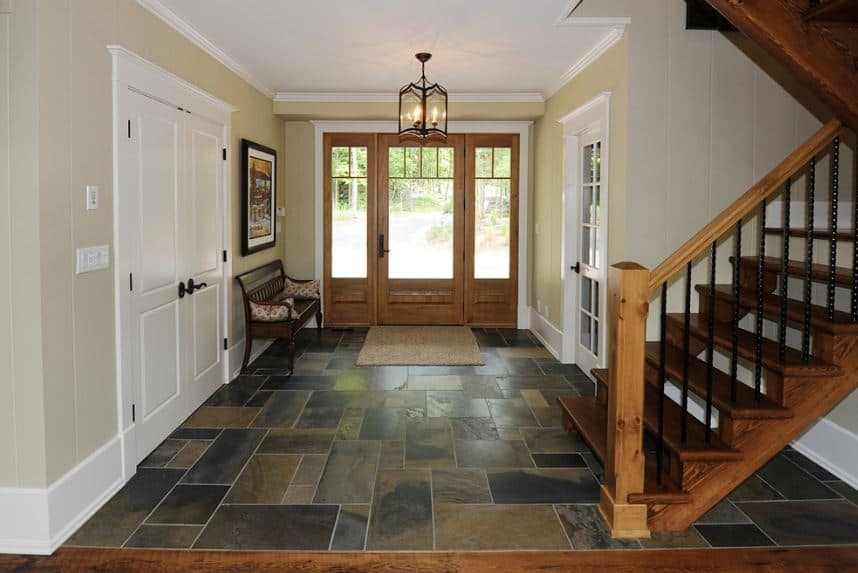 Dark-hued tiles adorn the floor of this Craftsman-Style foyer. A comfortable wooden bench is placed by the door for the waiting guests. Above the bench is a framed painting mounted on the beige wall that is given a warm light by the semi-flush lamp mounted on the white ceiling.