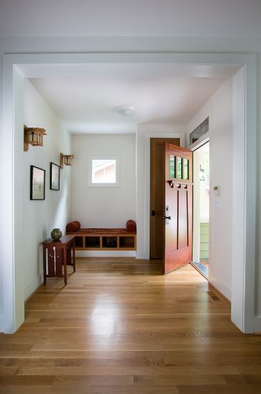 This Craftsman-Style foyer has a white alcove fitted with a built-in wooden bench that doubles as a shoe rack. This shoe rack matches well with the console table that stands across the entrance of the redwood main door. Above the console table is wall-mounted artworks that are flanked by wall lamps.