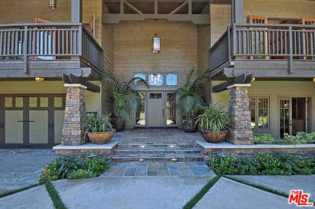 This Craftsman-Style landscape has gorgeous stone ledges and pillars that border the walkway leading to the main door. The main door is flanked by palm trees planted on huge pots that complement the stone walkway that has installed lights.