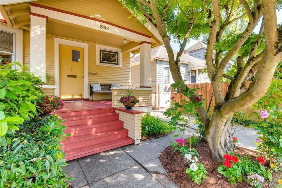 This Craftsman-Style landscape is dominated by a charming gnarled tree that looks like it came out of a fairytale. This tree is surrounded by colorful flowers that stand out against the gray stone walkway leading to redwood steps flanked with potted plants.