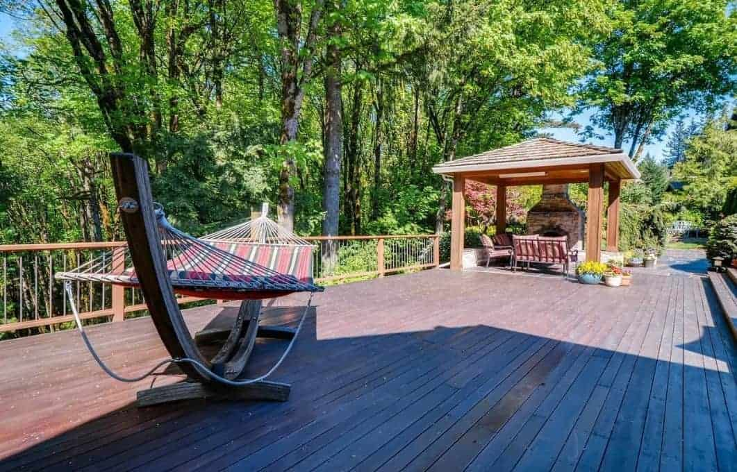 The surrounding forest is a perfect background for the Craftsman-Style landscape of this house bringing with it a serene quality that you can enjoy with a hammock and a wooden gazebo. This gazebo has a set of comfortable chairs facing an outdoor stone fireplace.