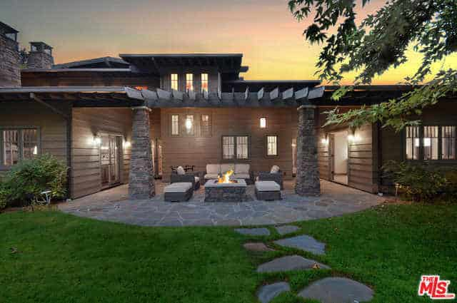 This charming backyard has stone flooring matched with stone structures built into it. There is an open square hearth made of stone that is flanked by a pair of stone pillars that hold up the wooden trellis. The well-manicured lawn perfectly complements the wooden quality of the house.