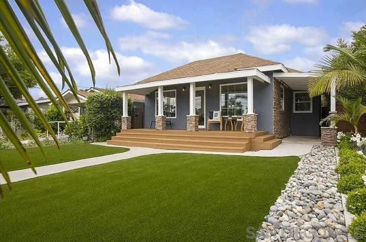 This Craftsman-Style landscape has impeccable carpets of Bermuda grass that looks so perfectly pristine that it looks like a part of a golf course. In the middle of these grass lawns is a stone walkway leading up to wooden steps that lead up to a peaceful front porch.