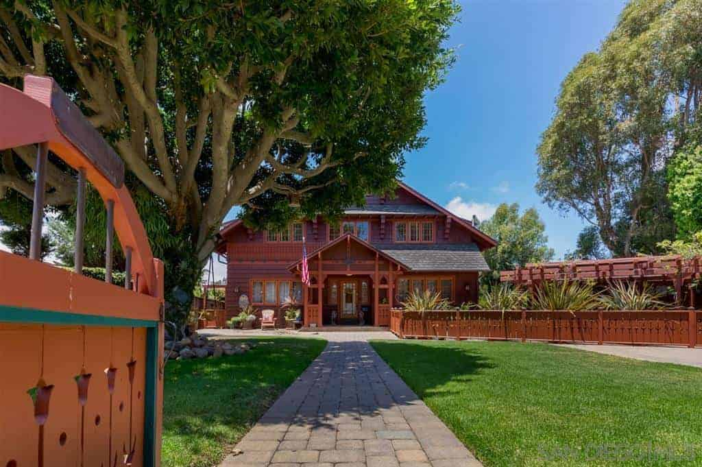 The wooden gate of this Craftsman-Style landscape leads to a stone walkway that is flanked by pristine grassy lawns in an open area. A huge gnarled tree with thick leaves gives this open area a serene patch of shadow against the sun. A fence of redwood surrounds this peaceful front lawn.