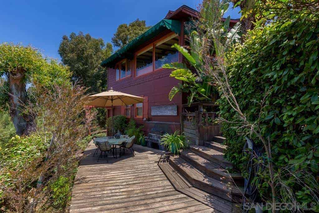 The house is surrounded by wooden flooring and steps that lead to an open area with a background of the surrounding nature. This is augmented by the potted plants and palm trees that stand in contrast to the redwood sides of the house.