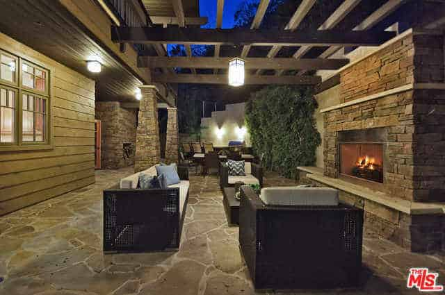 This Craftsman-Style landscape outside the house is well-lit with warm yellow lights coming from the pendant light hanging from the wooden trellis. This light is augmented by the outdoor fireplace that is fixed into the wall with a stone structure bordered with ledges that match the stone flooring.