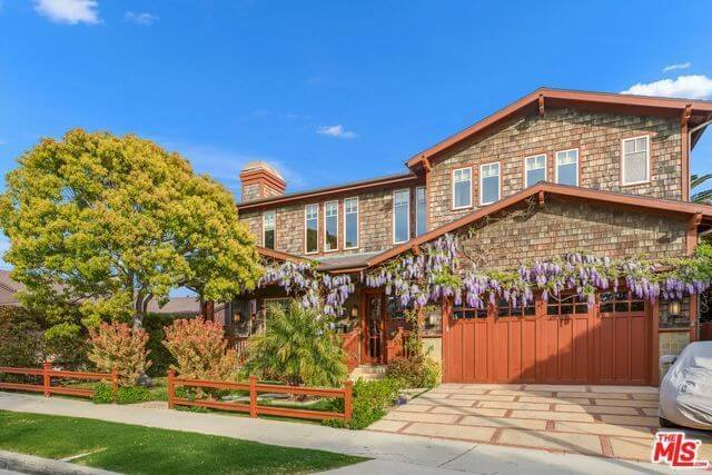 The purplish flowers hanging from the vines that run along the walls of the wooden house provide a beautiful centerpiece to this Craftsman-Style landscape. It is paired with a tree surrounded by various plants and fenced in with wood that matches the hue of the garage door.