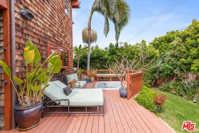This is a comfortable area shadowed by the house. It is complemented by redwood flooring that leads to the jacuzzi that is surrounded by potted plants. There are also lawn chairs and benches that provide comfortable white cushions that contrast the redwood elements.