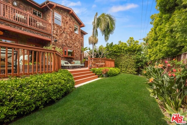 This backyard has redwood handcrafted railings that flank the wooden steps down to a well-maintained lawn of Bermuda grass. The grassy lot is lined with thick shrubs on one side and tropical plants on the other side that lines the wooden wall.