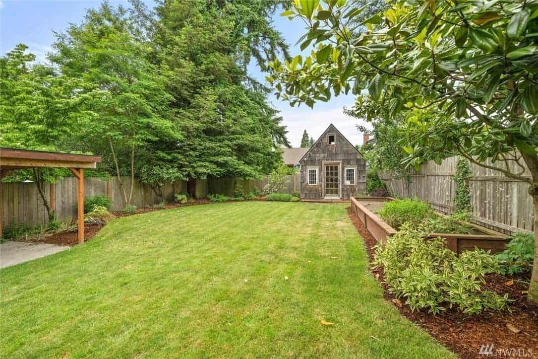 This wide and spacious Craftsman-Style landscape is perfect for parties and barbecues over the carpet of grass. It is surrounded by wooden fences that are complemented by the abundant tall trees and plant life that lines the sides of the grassy lawn.