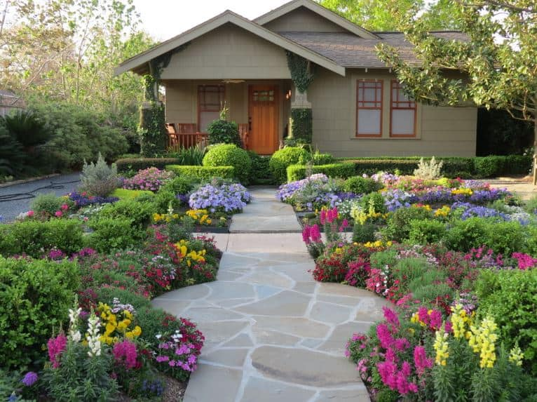 The short walk towards the front porch of the house is a visual delight with a stone walkway surrounded by colorful flowering shrubs with hues of varying white, pink, purple, blue and yellow. This rainbow garden is bordered by well-manicured hedges when you reach the house.