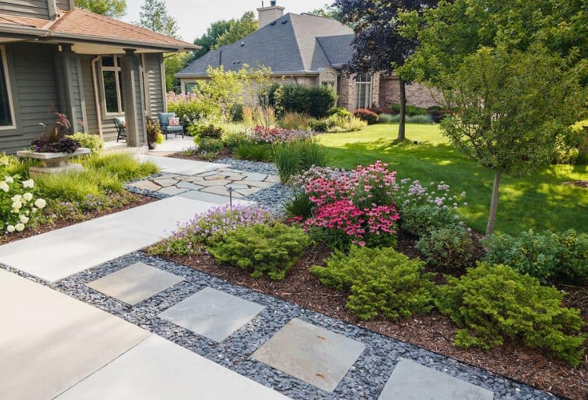 A lovely arrangement of various stone steps serves as a walkway that leads to the front porch that has a couple of comfortable chairs to enjoy the view and entertain guests. The front yard is filled with colorful flowering shrubs and medium-sized trees.