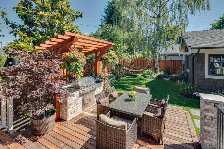 This landscape is specially made for spending a lovely weekend with friends and family. There is an outdoor dining area partnered with a modern grilling station topped by wooden trellis. For maximum comfort, there is a hammock under the shades of a tall tree.