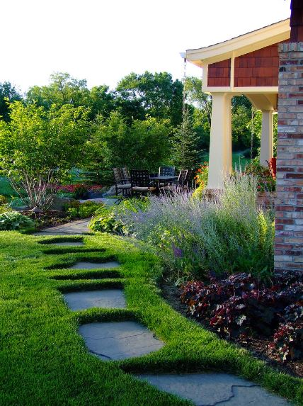 The lovely irregular stone steps seem like they are sinking into the lush carpet of grass that surrounds the house. This effect is enhanced by the colorful shrubberies that leads to an outdoor dining area with a round table surrounded by dark chairs.