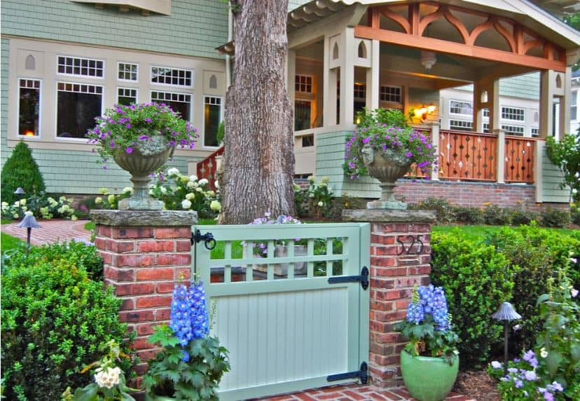 A pair of low brick columns flank the wooden gate of this charming front yard. The brick columns are paired with potted flowers that have a contrasting blue hue. The walkway is also made of bricks and winds around the huge trunk of a tree towards the front porch.