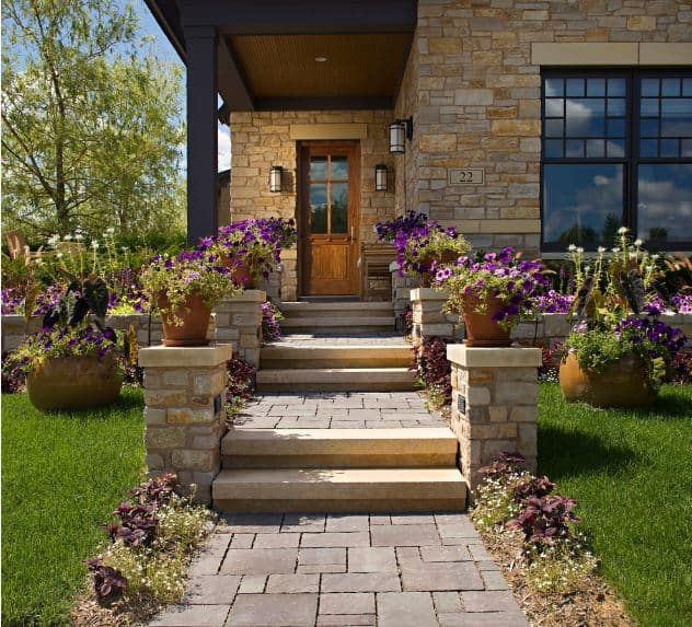 Stone steps are flanked by small stone columns that offer up purple potted flowers to those who walk up to the main door. The main door has a wooden bench on the side and is illuminated by wall-mounted lamps that go well with the stone walls of the house.