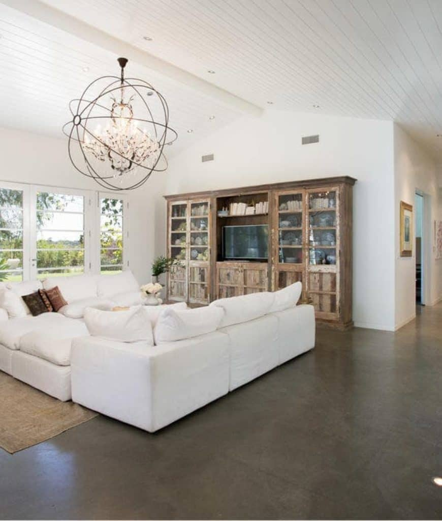 A rustic cabinet on a concrete flooring stands out in this white living room with comfy seats and a spherical chandelier that hung from the shiplap ceiling.