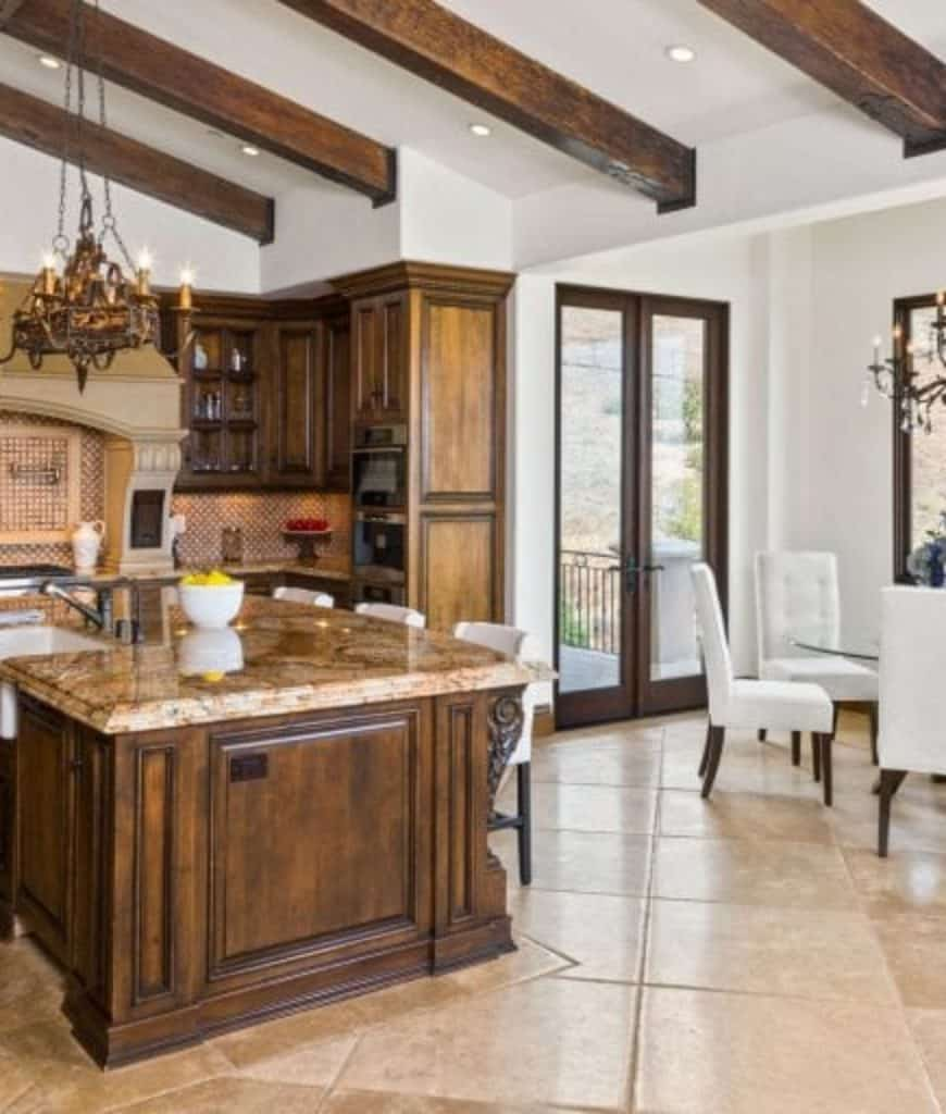 Dine-in kitchen offers white high back chairs that complement with the bar stools sitting at a wooden breakfast island that's topped with marble counter and porcelain vessel sink.