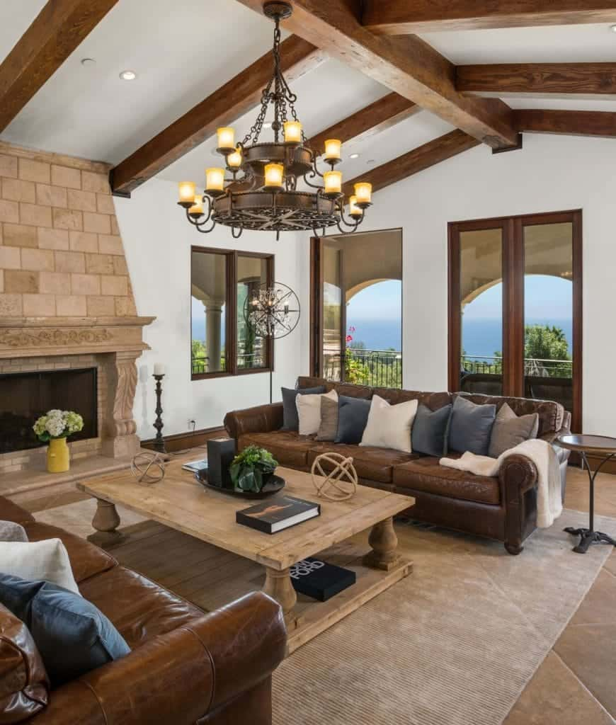 Rustic living room with a stone fireplace and a wrought iron chandelier that hung from the wood beam ceiling. It includes brown leather facing sectionals with a natural wood coffee table in the middle.