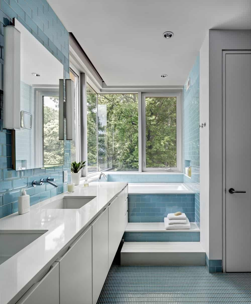 This master bathroom features stylish blue tiles floors and walls. The room also offers a corner tub near the windows and a double sink.