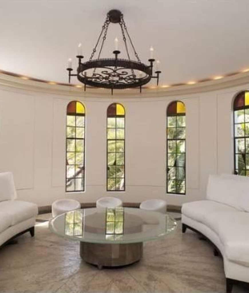 Round living room offers curved sectionals and white stools surrounding a glass top coffee table illuminated by a wrought iron chandelier.