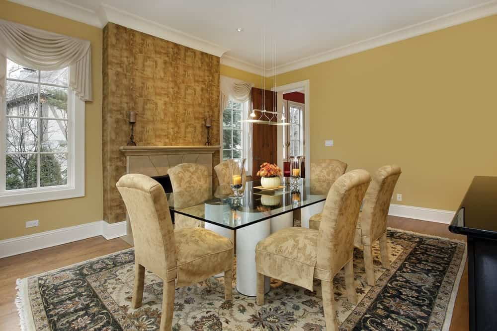 Yellow dining room illuminated by a pendant light that hung over a glass top dining table surrounded with beige skirted chairs. It includes a fireplace fixed to the pillar that's clad in lovely wallpaper.