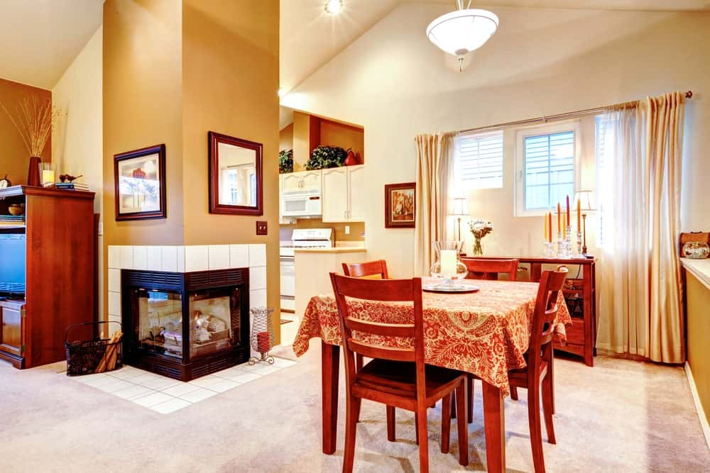 Warm dining room decorated with framed wall art and mirror that are mounted above the double sided fireplace fitted to the tan pillar. It has a buffet table that complements with the wooden chair and dining table topped with a patterned cover.