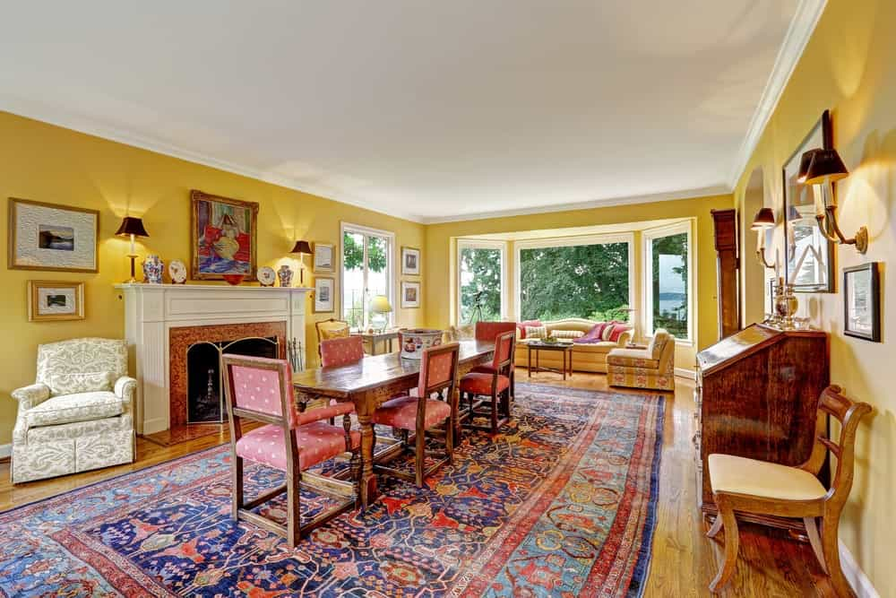 An open dining area showcases a natural wood dining table surrounded with red dotted chairs that sit on a huge rug. There's a fireplace fixed to the yellow wall accented with lovely wall arts and decors.