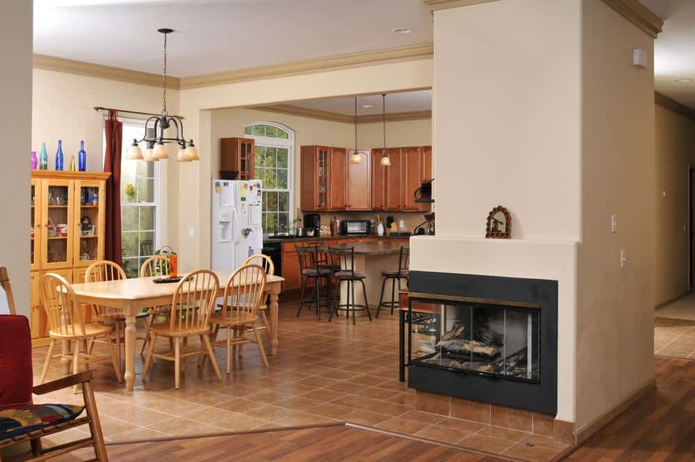 An eat-in kitchen with a wooden dining set complementing with the display cabinet that's topped with multi-colored bottles. It has a modern fireplace fixed to the beige pillar lined with crown molding.