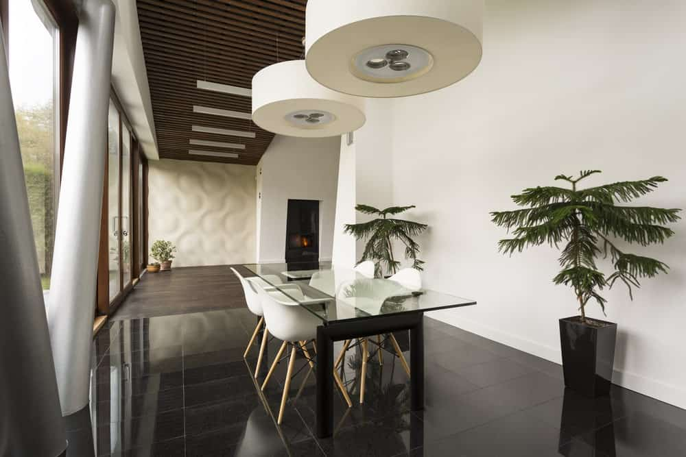 Fresh dining room illuminated by a pair of oversized round pendants that hung over a glass top dining table paired with white contemporary chairs.