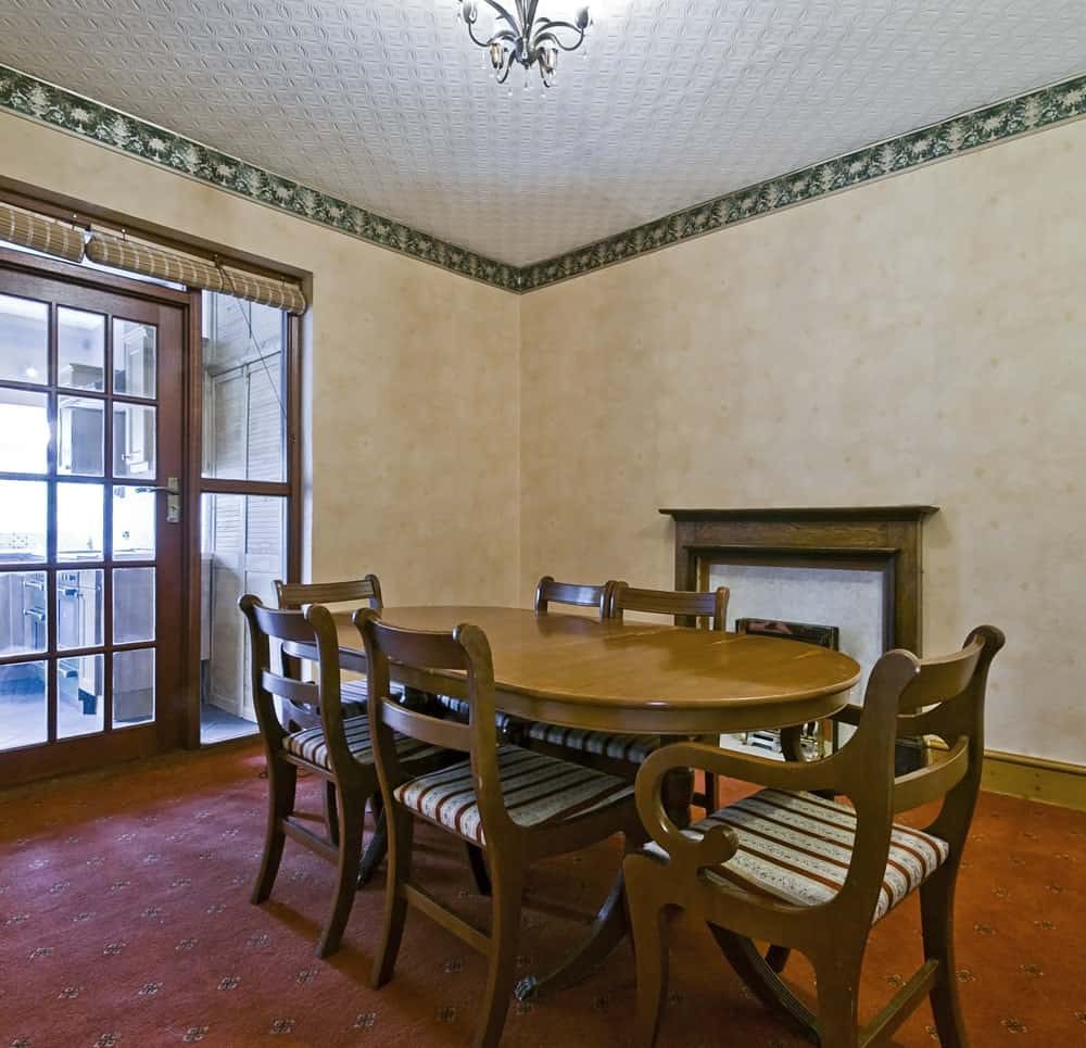 This dining room features an oval dining table paired with striped cushioned chairs over carpet flooring. It is lighted by a semi-flush light mounted on the white textured wall lined with green patterned crown molding.