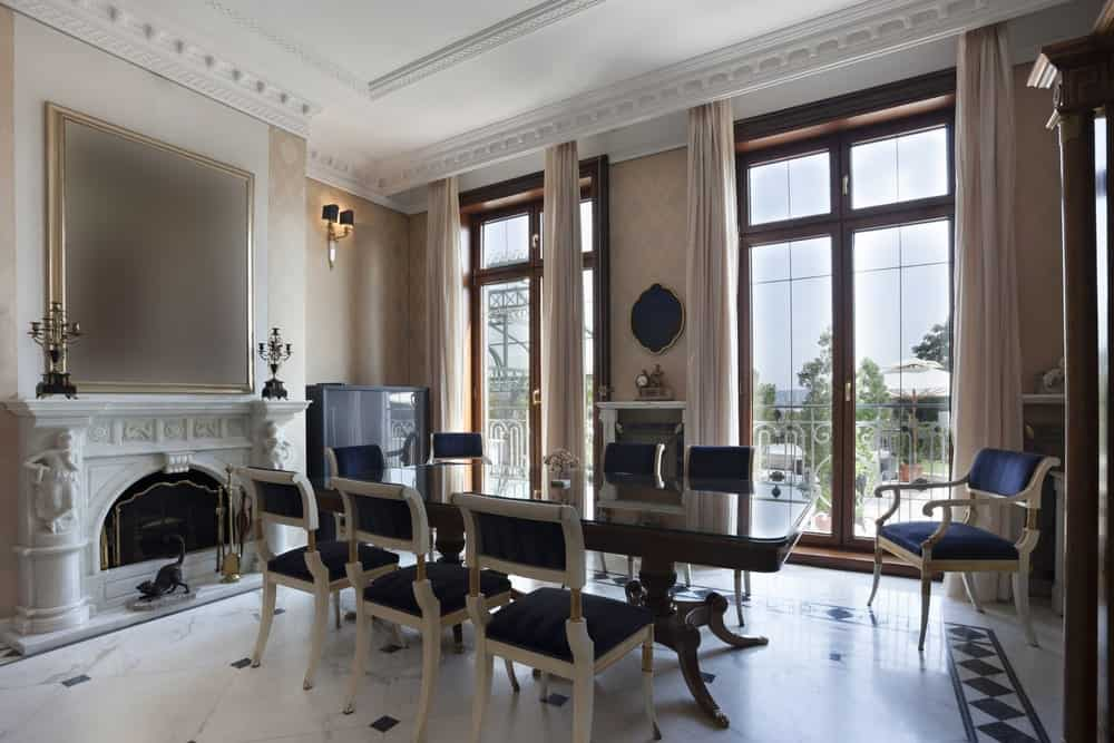 Elegant dining room with white marble flooring and full height glazing covered with sheer curtains. It has a rectangular dining table that's accented with classy deep blue chairs.