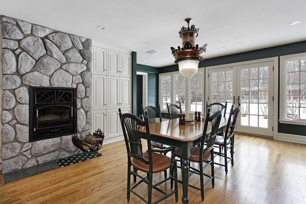 Airy dining room showcases hardwood flooring and white framed glass windows and french door overlooking a serene outdoor view. It has a wooden black dining set and a modern fireplace fitted on the stone wall next to the white cabinetry.