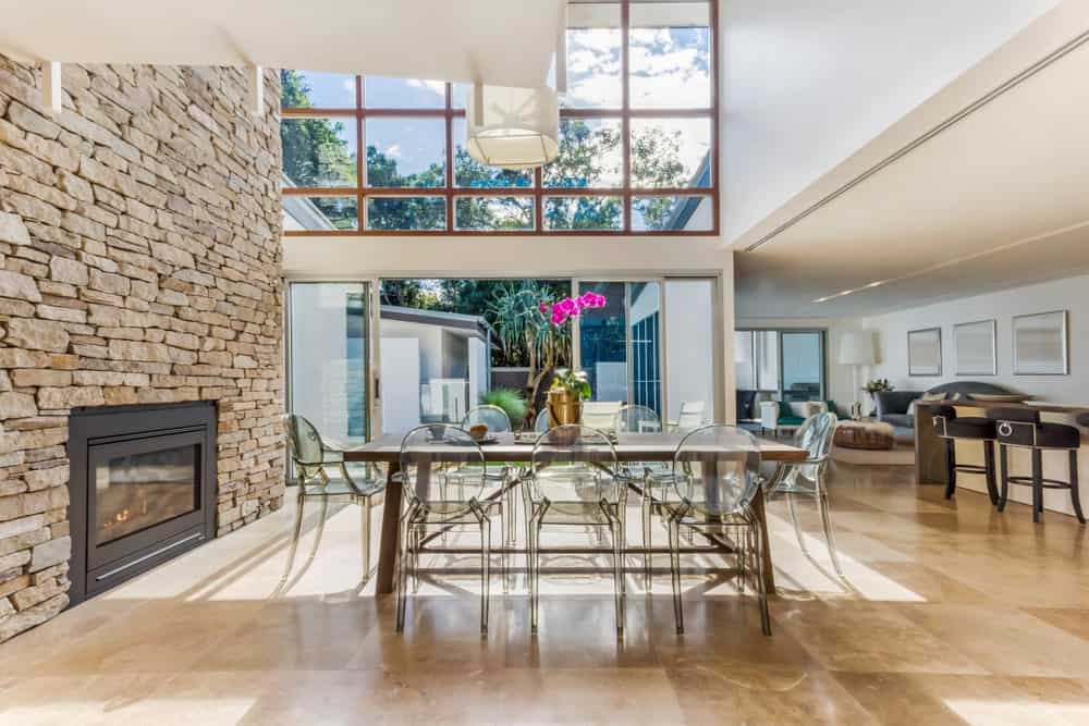 Bright dining room illuminated by a white drum pendant that hung over a wooden dining table and glass round back chairs. There's a black fireplace fixed to the stone brick accent wall adjacent to the glass paneled windows and sliding glass doors.