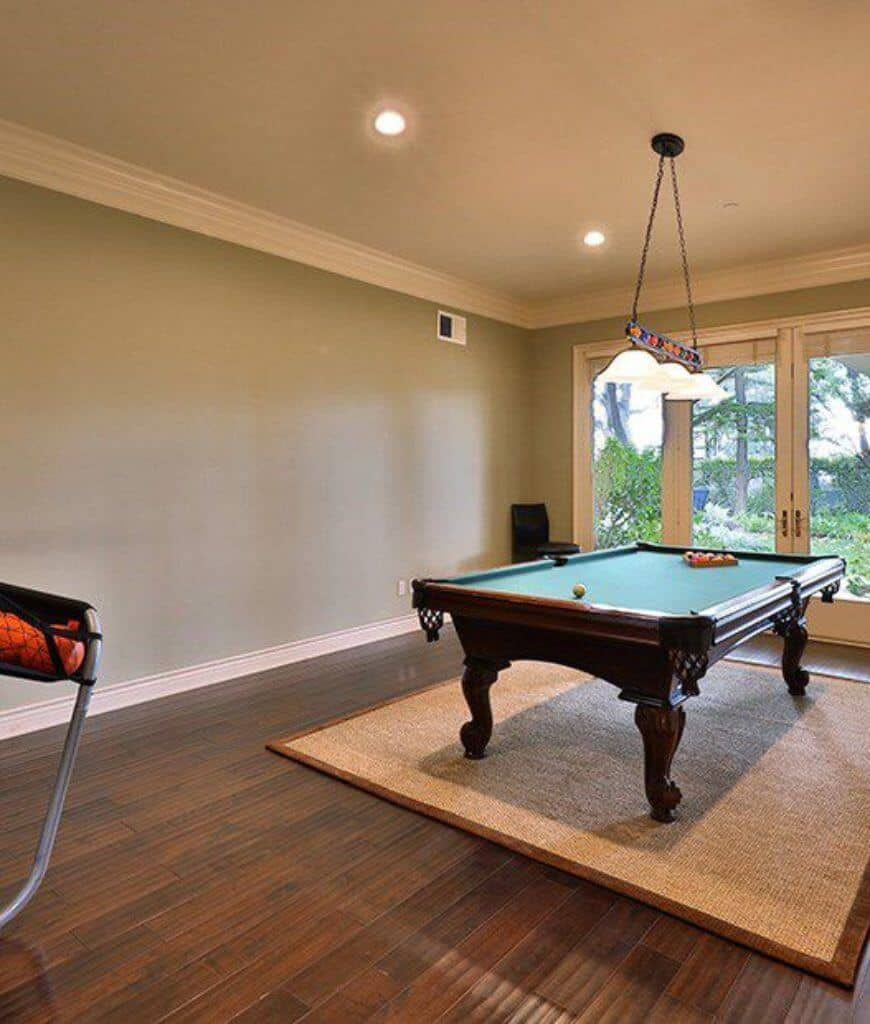 This room boasts a traditional pool table that sits on a woven rug lighted by glass pendants. It has wood plank flooring and a French door that leads to the lush green yard.