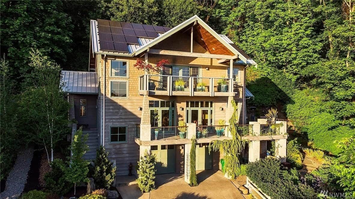 This charming house goes perfectly well with the surrounding greenery of its landscape. The two balconies have railings that are adorned with potted plants that provide a nice view for the glass doors of each level. The high roofs are fitted with solar panels giving this house a green personality.