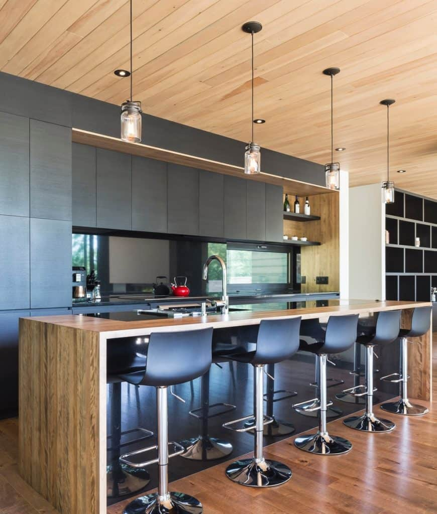 Contemporary kitchen with black cabinetry and breakfast bar topped with a smooth wooden counter and lined with black bar stools and glass pendants that hung from the wood plank ceiling.