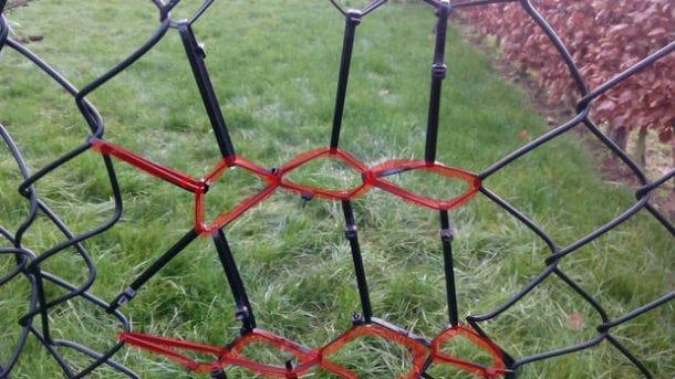 A broken fence fixed with zip ties.