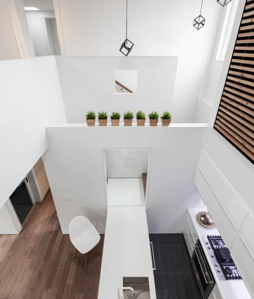 Top view of the minimalist kitchen featuring cube pendant lights and white walls accented with small potted plants that create a refreshing ambiance to the area.