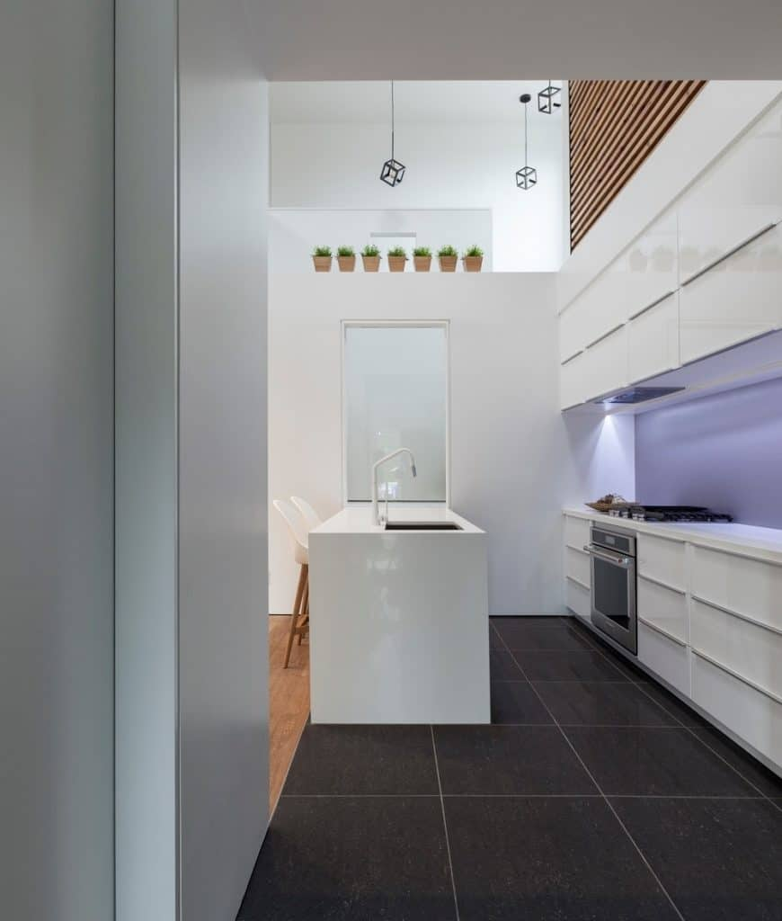 Minimalist kitchen with white cabinetry and sleek breakfast bar fitted with a sink and white faucet. It has black tiled flooring and a towering ceiling with hanging cube pendants.